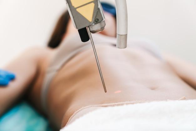Portret kaukaskiej kobiety podczas zabiegu depilacji laserowej przez specjalistę w rękawiczkach leżących na łóżku w salonie kosmetycznym