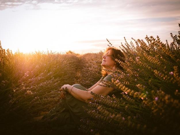 Portret kaukaskiej kobiety w pięknym widoku o zachodzie słońca