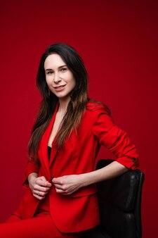Portret kaukaskiej kobiety z długimi ciemnymi prostymi włosami w czerwonym garniturze biurowym, czarnych butach siedzi na czarnym krześle