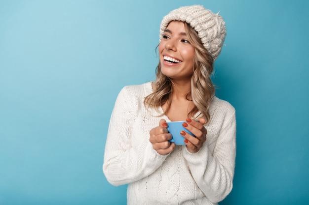 Portret kaukaskiej radosnej kobiety w białym kapeluszu śmiejącej się i trzymającej filiżankę odizolowaną na niebiesko