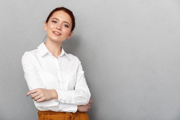 Portret kaukaskiej rudej bizneswoman 20s w formalnym stroju uśmiecha się i pozuje w biurze na białym tle nad szarym