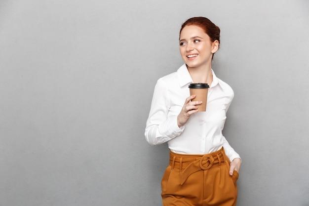 Portret kaukaskiej rudej bizneswoman 20s w wizytowym stroju uśmiechający się w biurze i pijący kawę na wynos z plastikowego kubka na białym tle nad szarym