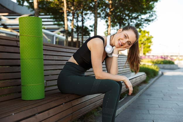 Portret kaukaskiej sportsmenki w dresie uśmiechający się siedząc na ławce z matą fitness w parku miejskim