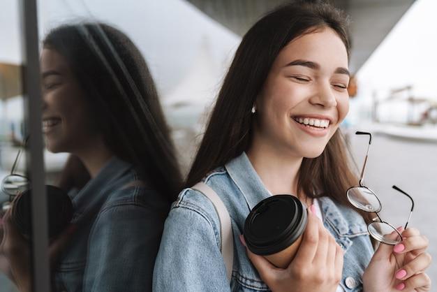Portret kaukaskiej uśmiechniętej nastoletniej dziewczyny w dżinsowej kurtce trzymającej okulary i papierowy kubek kawy na wynos podczas chodzenia na zewnątrz