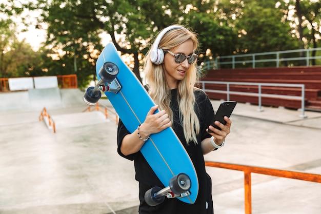 Portret kaukaskiej zadowolonej kobiety w słuchawkach i okularach przeciwsłonecznych, piszącej na telefonie komórkowym, trzymając deskę w skateparku