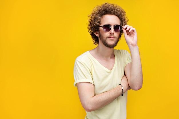 Portret kędzierzawy z włosami młody człowiek patrzeje w zmieszany w okularach przeciwsłonecznych i bermudach