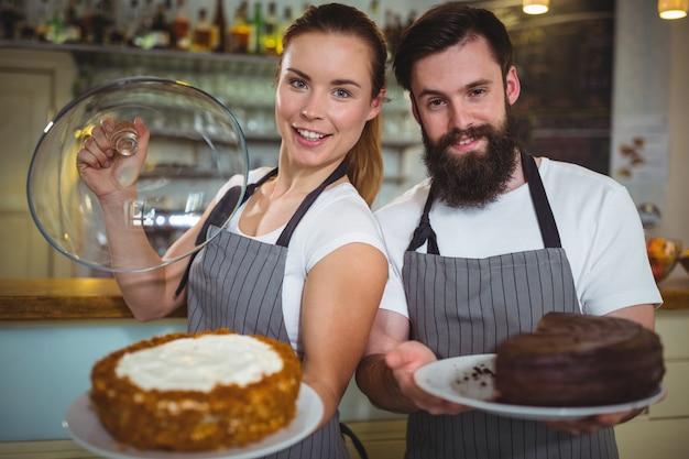 Portret kelner i kelnerka trzyma talerz ciasta
