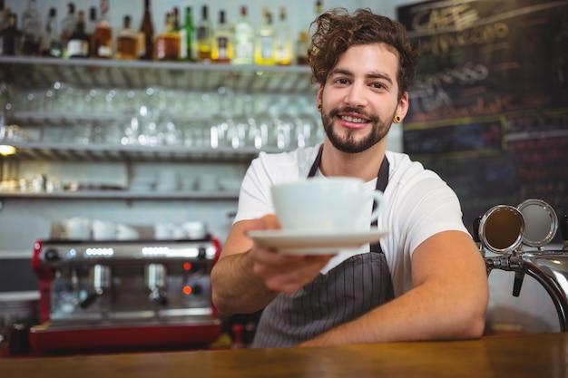 Portret kelner serwuje kawę na licznik