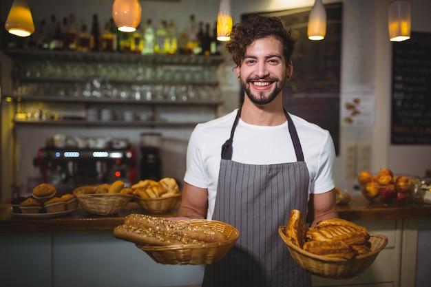 Portret kelner trzyma kosz z chlebem