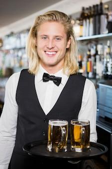 Portret kelnera trzymając zasobnik z kufle do piwa