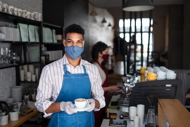 Portret kelnera z maską serwującą kawę w kawiarni małej firmy