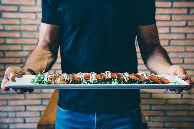 Portret kelnera z talerzem pomidorowym i anchois rybnymi. koncepcja gotowania