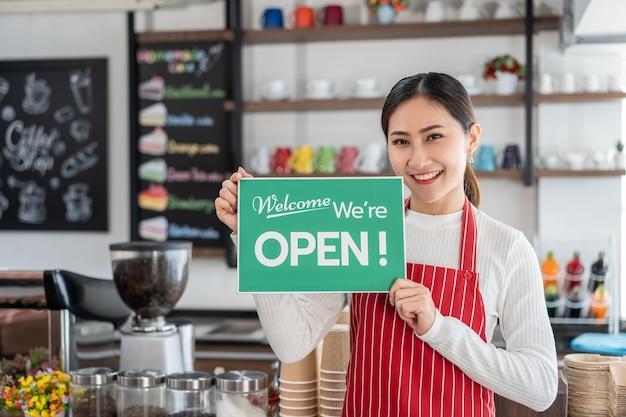 Portret kelnerka pokazuje otwarty szyld w kawiarni
