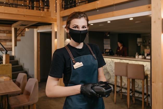 Portret kelnerka trzyma bezprzewodowy terminal płatniczy