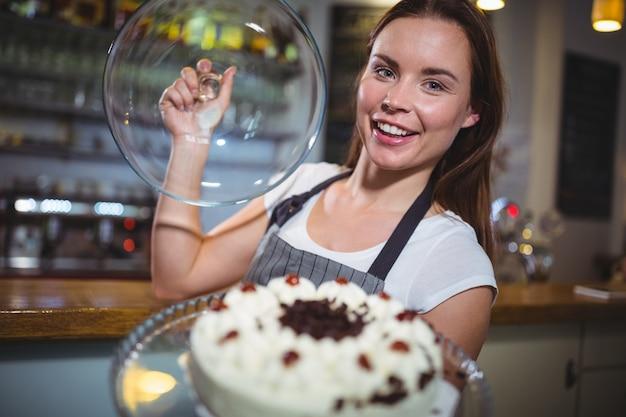 Portret kelnerka trzyma talerz ciasta
