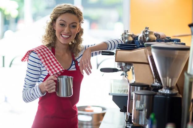 Portret kelnerki pozycja z dzbankiem przy kontuarem