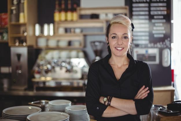 Portret kelnerki pozycja z rękami krzyżować
