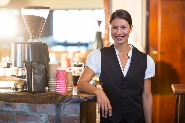 Portret kelnerki stojącej przy kasie