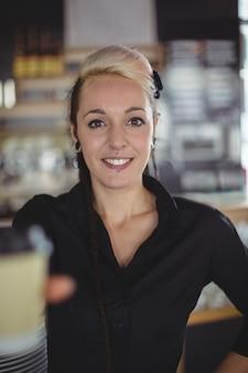 Portret kelnerki stojący z filiżanki kawy jednorazowe
