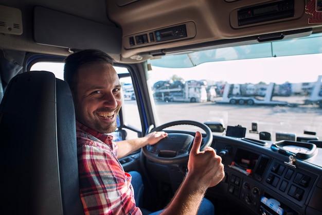 Portret kierowca ciężarówki siedzi w jego ciężarówce, trzymając kciuki do góry