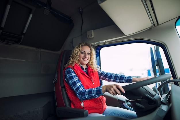 Portret kierowca ciężarówki siedzi w kabinie ciężarówki z rękami na kierownicy