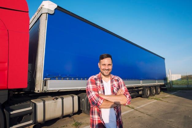 Portret kierowca ciężarówki w średnim wieku z rękami skrzyżowanymi stojący przy przyczepie ciężarówki gotowy do jazdy