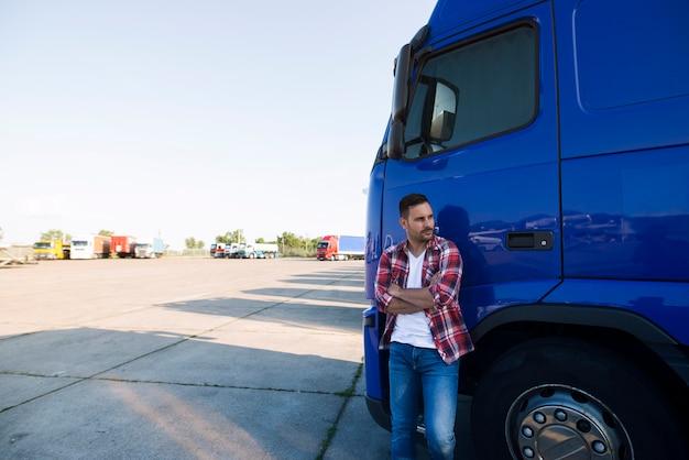 Portret kierowca ciężarówki w ubranie, stojąc przy swoim pojeździe ciężarówki i patrząc na boki