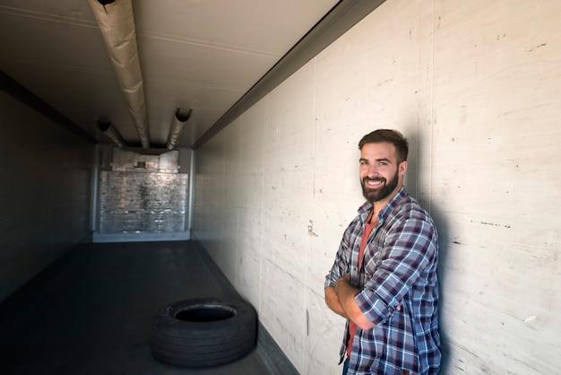 Portret kierowcy ciężarówki ze skrzyżowanymi rękami stojącego w pustej przyczepie ciężarówki