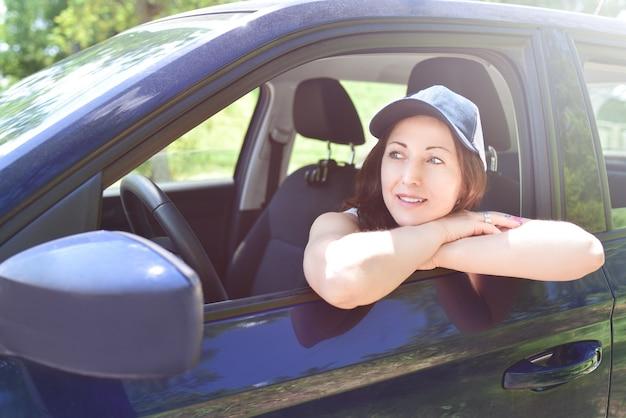 Portret kierowcy kobiety spoglądającej na samochód w kapeluszu, patrząc przez okno