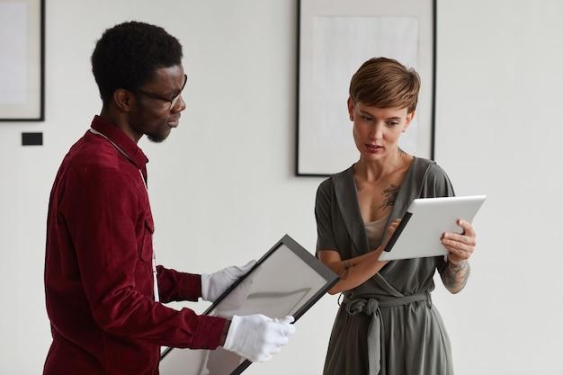 Portret kierowniczki galerii sztuki w pasie za pomocą cyfrowego tabletu, instruując pracownika trzymającego ramki do malowania i planującego wystawę w muzeum,