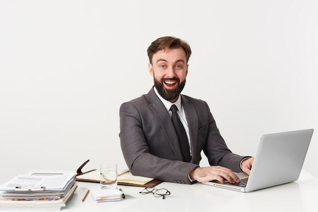 Portret kierownika biura, który uśmiecha się szeroko, słysząc zabawny dowcip, siedzi przy biurku w biurze, pracuje dla swojego laptopa, ubrany w drogi garnitur z krawatem, lubi swoją pracę.