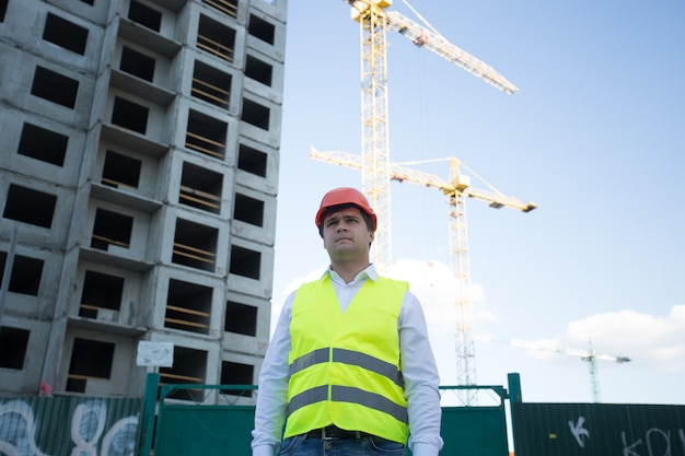 Portret kierownika budowy pozującego przed dźwigami i placem budowy