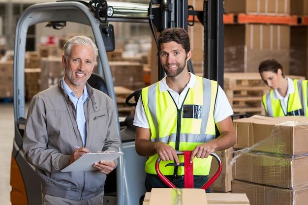 Portret kierownika magazynu i pracowników przygotowujących przesyłkę