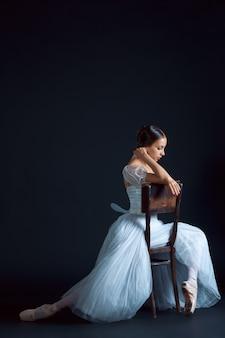 Portret klasycznej baleriny w białej sukni na czarnej ścianie