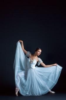 Portret klasycznej baletnicy w białej sukni na czarnej przestrzeni