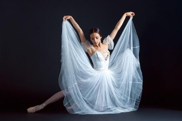 Portret klasycznej baletnicy w białej sukni na czarnym tle