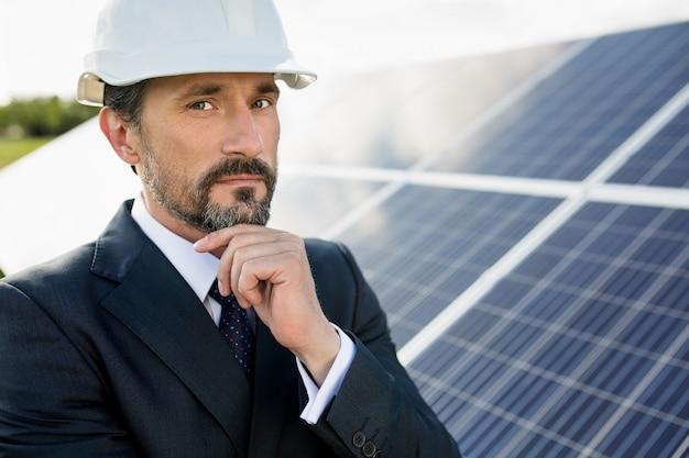 Portret klienta w białym kasku w elektrowni słonecznej.