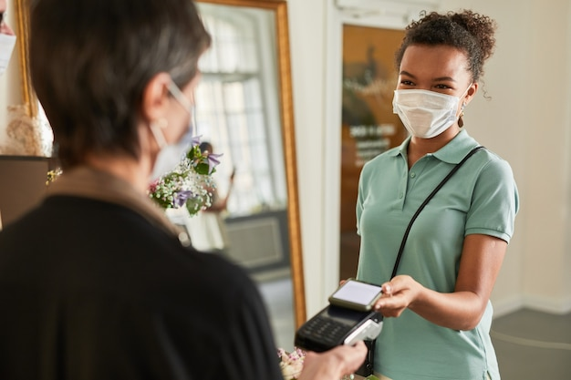 Portret klientki płacącej za pośrednictwem smartfona w kwiaciarni i noszącej miejsce na maskę