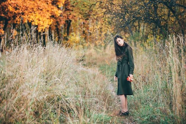 Portret kobiecego piękna otoczony żywymi liśćmi.