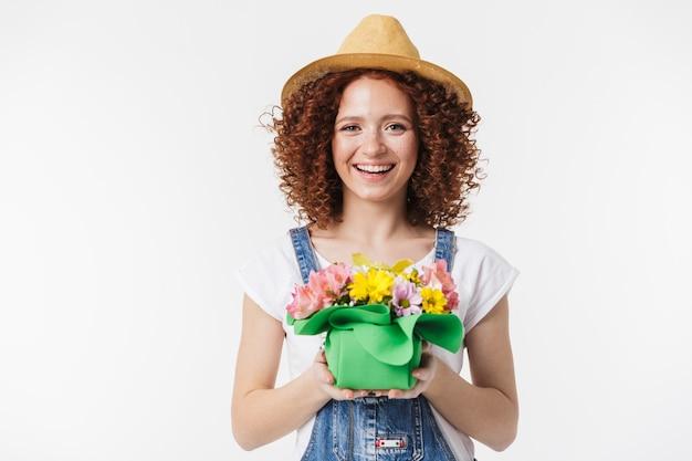 Portret kobiecej rudowłosej kręconej kobiety 20 lat w letnim słomkowym kapeluszu uśmiecha się i trzyma pudełko na kwiaty izolowane nad białą ścianą
