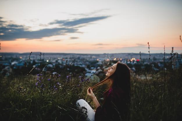 Portret kobiecy, natura. kobieta w fiołkowej koszula siedzi na trawie