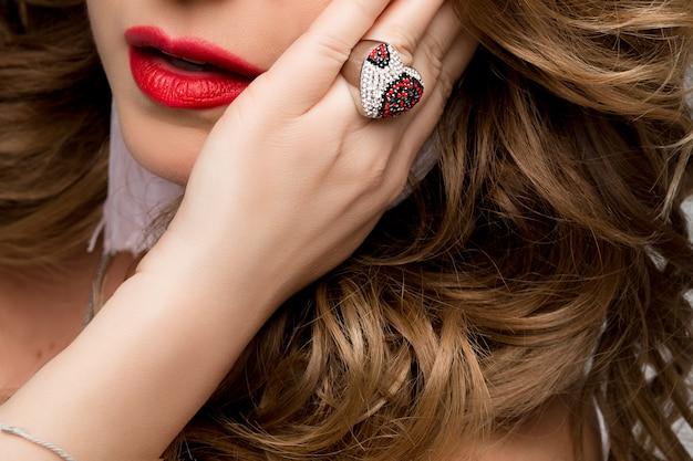 Portret kobiecych ust i dłoni z pierścionkiem.