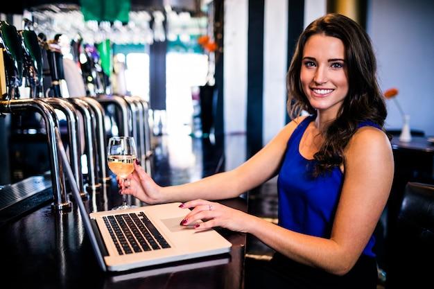 Portret kobieta używa laptop i mieć napój w barze