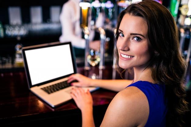 Portret kobieta używa laptop w barze