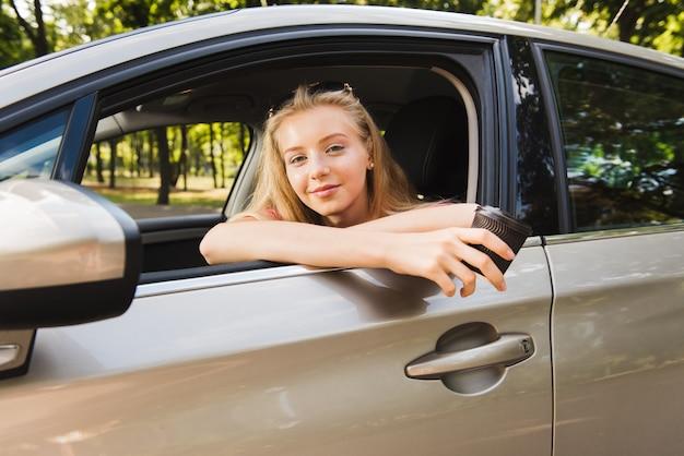 Portret kobieta w samochodzie z papierową filiżanką