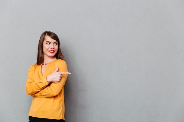 Portret kobieta wskazuje palec daleko od przy kopii przestrzenią
