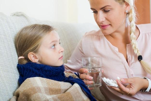 Portret kobieta z antybiotycznym i dzieckiem ma grypę
