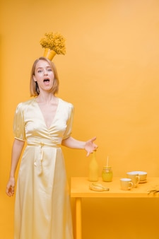 Portret kobieta z kwiatu garnkiem na głowie w żółtej scenie