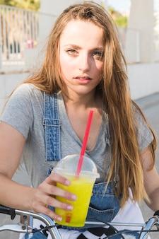 Portret kobieta z rowerowym trzyma szkłem sok