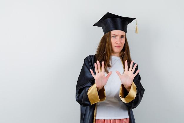 Portret kobiety absolwent pokazując gest stopu w ubranie, mundur i pewny siebie widok z przodu